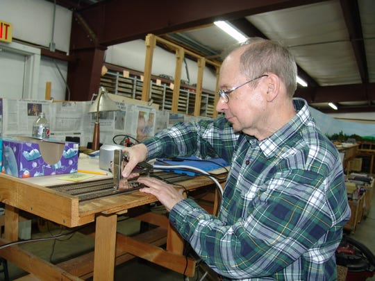 Associated Model Railroad Engineers of Coshocton charter member Rick Jones works on track by hand during one of the group's Friday night sessions.