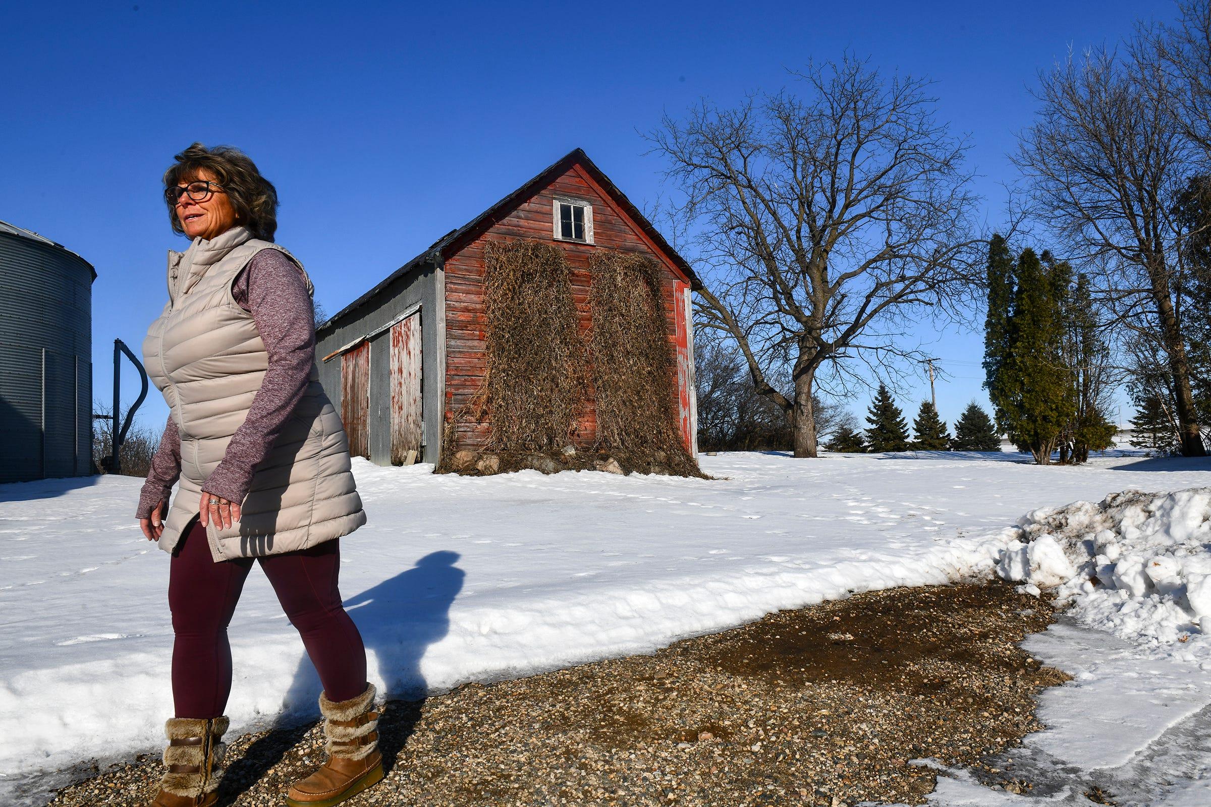 Barb Ruhland walks between buildings Wednesday, Feb. 5, 2020, on her farm near Watkins, Minn.