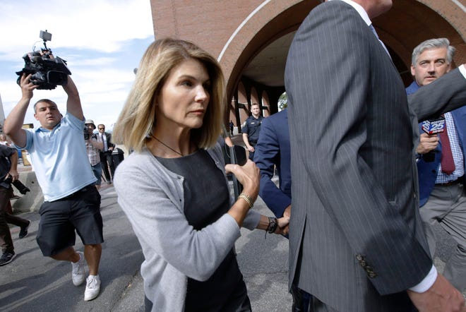 In this file photo dated August 27, 2019, actress Lori Loughlin leaves the federal court in Boston after hearing in a nationwide bribery scandal for university admissions. Loughlin, her husband as fashion designer Mossimo Giannulli, and nine other parents are facing new charges in the college admissions scandal. The federal prosecutor announced on Tuesday, October 22, 2019, that the parents were charged with conspiracy to bribe the federal program.