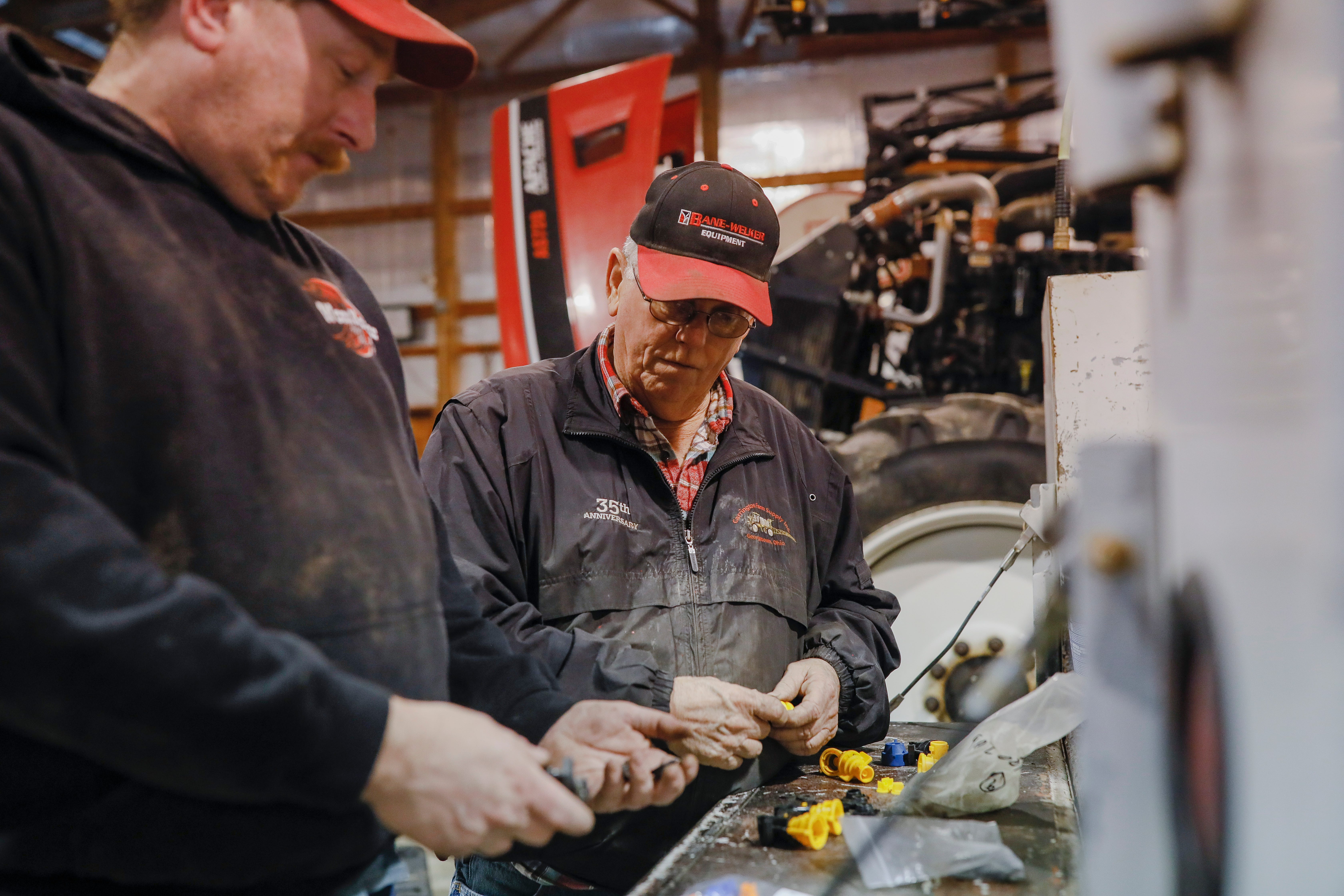 Charlie Utter does some service work with his son, Kyle, left, at their farm on Tuesday, March 3, 2020 in Georgetown, Ohio. Utter's cousin, Steve, died by suicide in July 2017. [Joshua A. Bickel/Dispatch]