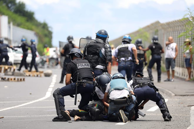 French police officers arrest a demonstrator in Le Port on March 1, 2020, as people protest the arrival of the passengers of the Sun Princess cruise ship on the Indian Ocean island of La Reunion.