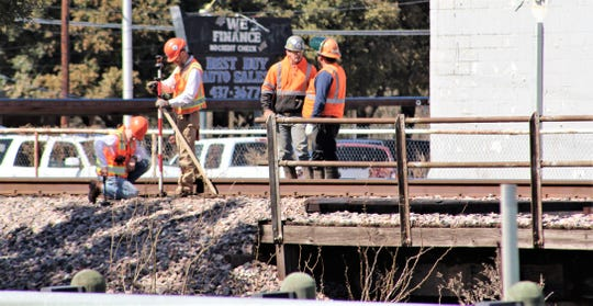 Workers take measurements at a small railroad track bridge in west Abilene on Thursday. Union Pacific is upgrading several bridges in and near Abilene.