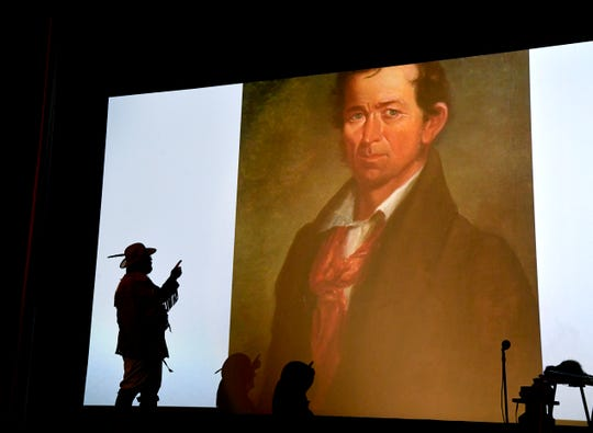 """Dr. Christopher Hull stands before a projection of his ancestor, Erastus """"Deaf"""" Smith on the screen of the Majestic Theatre. Hull was lecturing in Eastland Thursday about the Texas founding father."""