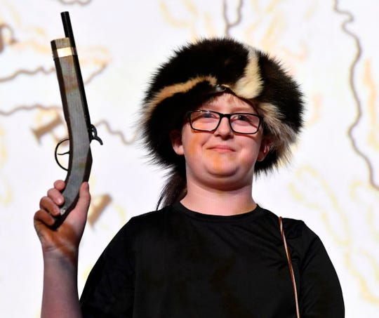 """Hayden Dobbs, a fourth-grader at Ranger Elementary School, holds a toy pistol and wears a skunk skin hat during a presentation on Texas pioneer Erastus """"Deaf"""" Smith on Thursday. Dr. Christopher Hull, a descendant of Smith, performed a reenactment of him and a history lesson for students at Eastland's Majestic Theatre."""