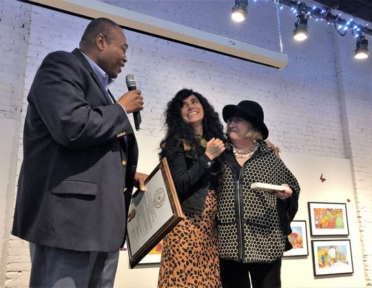 Mayor Anthony Williams, left, holds the proclamation he read to Mexican author-illustrator Yuyi Morales, center, at a luncheon Wednesday at the National Center for Children's Illustrated Literature. Councilwoman Donna Albus presented Morales with a key to the city. Morales' exhibition, Sonadores, can be viewed through May 28.
