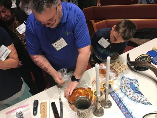 Rabbi Craig Mayers of Temple Beth Sholom in Melbourne shares a sample of challah bread with the congregation.