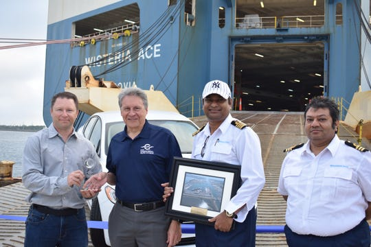 Port Canaveral Chief Executive Officer John Murray, second from left, presents welcome plaques to Ross Teague, left, Capt. Jayanta Sarkar and Capt. Arinjit Guha of the Wisteria Ace.