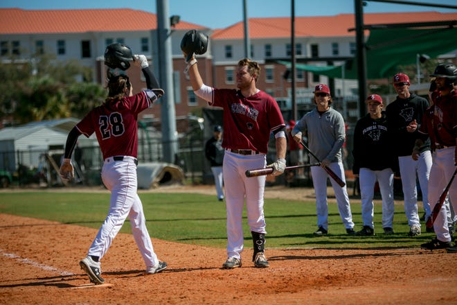 Brett Parrish is greeted by his Florida Tech teammates after crossing home plate.