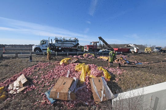 Workers clean up bulk raw pork that spilled onto U.S. 30 early Thursday morning. Traffic had to be rerouted through Bucyrus until the eastbound lane could be cleared.
