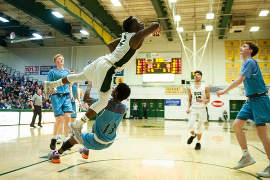 Rice's Michel Ndayishimiye (2) leaps over South Burlington's Khalon Taylor (13) for a layup during the second game of the boys basketball semi finals between the South Burlington Wolves and the Rice Green Knights at Patrick Gym on Wednesday night March 4, 2020 in Burlington, Vermont.
