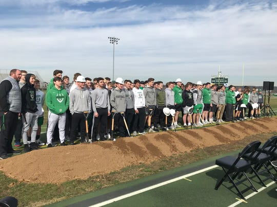 Harrison High School football players appear at the school's ground breaking ceremony for the new artificial turf that will be installed.