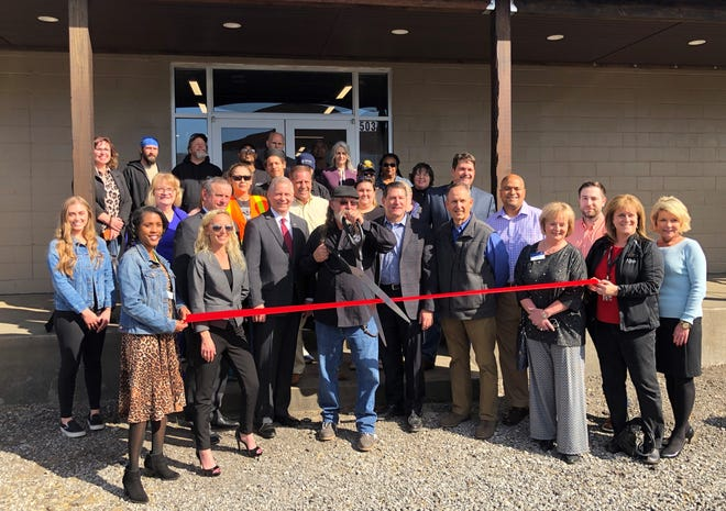 Local officials, volunteers, and chamber of commerce members join Manna Cafe Ministries founder Kenny York, center, for the ribbon cutting ceremony of York's newly completed Refuge Community Center in Clarksville, Tenn., on Thursday, March 5, 2020.