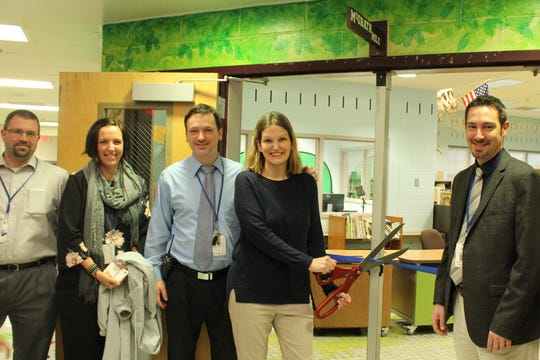Michael Pate, supervisor of buildings and grounds; Stacey Modugno, curriculum supervisor; Jeffrey Heaney, principal of Woodland School; Amanda McGrath, library media specialist and Dr. Matthew Mingle, superintendent of schools smile for a picture just before McGrath cuts the ceremonial ribbon.
