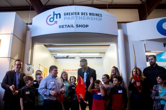 Jay Byers, CEO of the Greater Des Moines Partnership, helps studnets from Norwalk cut the ribbon on the new Junior Achievement of Central Iowa's BizTown retail store, sponsored by the Greater Des Moines Partnership on Thursday, March 5, 2020, in West Des Moines.