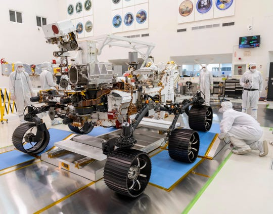 """Engineers watch the first driving test for the Mars 2020 rover in a clean room at the Jet Propulsion Laboratory in Pasadena, Calif. on Dec. 17, 2019.  On Thursday, NASA announced the explorer's name will be """"Perseverance."""""""