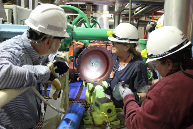 Contractors Sandi Branch, center, and Amy Kimberly of Pennsylania-based Day & Zimmerman perform diagnostic and maintenance work on an air operated valve (AOV) Wednesday at Davis-Besse Nuclear Power Station, as George Eades, staff nuclear specialist, looks on. The plant started its scheduled refueling and preventive maintenance Feb. 29, with more than 1,000 contractors expected to help with the outage and pump millions of dollars into Ottawa County's economy.