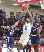 Florida Southwestern's Berrick Jeanlouis splits Gulf Coast State defenders Davonta Cook and Derrick Hardin during their FCSAA men's quarterfinal game in Niceville.
