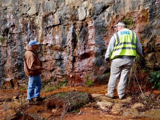 A DHEC employee looks at sediment seepage through the Lake Conestee dam.