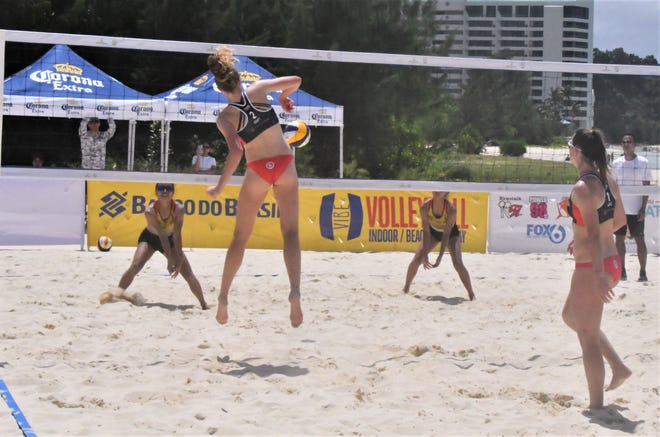 U.S. player Megan Kraft, left, takes a set from teammate Delayne Maple and slams one straight down against Guam's Melanie Damian and Alaunah Merto during the qualification tournament to Guam's first-ever FIVB sanctioned beach volleyball tournament March 5 at Jimmy Dee's Paradise Beach Resort & Bar in Tamuning.. The U.S. team beat the Guam first-timers 21-1, 21-0.