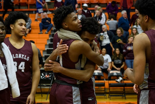 Henderson County's Myekel Sanners (21) embraces his teammate Daymian Dixon (3) after their season-ending loss to the Madisonville-North Hopkins Maroons in the Second Region Tournament held at Hopkinsville High School in Hopkinsville, Ky., Wednesday, March 4, 2020. The Colonels fell to the Maroons, 67-47.
