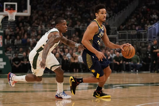 Indiana Pacers' Malcolm Brogdon drives past Milwaukee Bucks' Eric Bledsoe during the first half of an NBA basketball game Wednesday, March 4, 2020, in Milwaukee.