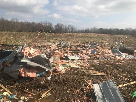 Remnants of Carl Frazee's trailer are scattered through a field across the road from where it originally sat before being hit by a tornado on Monday.