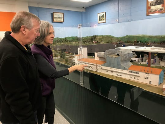 The Smoke Stack Hobby Shop owners Don and Patti Riordan show off a train set at the store that features a model of Anchor Hocking.