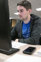 Brighton resident Collin Schafer, who is autistic, studies basic network establishment Thursday, March 5, 2020 in a cyber security course designed for matching the skills of people with autism with jobs in that field. The class is held at the Pinckney Cyber Training Institute.