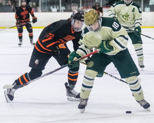 Everett Pietila (10), who scored Howell's second goal, battles for the puck with Brighton's Landon MacDonald in a regional championship hockey game on Wednesday, March 4, 2020.