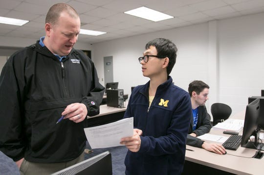 At left, Rich Lamb, coordinator of cyber operations at the Pinckney Cyber Training Institute, talks with student Tim Lee about his studies in a class at the institute which optimizes the skills of the autistic. In the background, Collin Schafer, who is autistic, works at the computer on classwork.