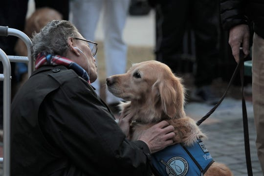 A comfort dog with Lutheran Church Charities K-9 Comfort Dog Ministry lets a man pet him during a vigil in the wake of the Molson Coors shooting.