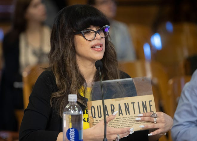 City of Milwaukee Health Commissioner Jeanette Kowalik holds a sign from the 1940s while speaking at a Public Safety and Health Committee meeting about coronavirus preparations March 5 at City Hall.