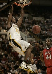 University of Wisconsin-Milwaukee's Joah Tucker slams during first half action as the University of Illinois at Chicago's Elliot Poole looks on Saturday, Feb. 5, 2005, during the Panthers game at the U.S. Cellular Arena in Milwaukee.