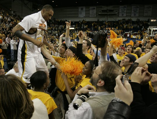 UW Milwaukee's James Wright puts on his Horizon League Champion shirt for the crowd after beating the Detroit Titans on March 8, 2005.