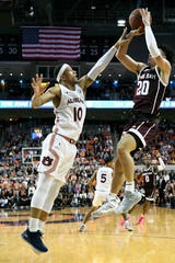 Texas A&M guard Andre Gordon (20) shoots over Auburn guard Samir Doughty (10) during the first half of an NCAA college basketball game Wednesday, March 4, 2020, in Auburn, Ala. (AP Photo/Julie Bennett)