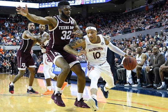 Auburn guard Samir Doughty (10) drives past Texas A&M forward Josh Nebo (32) during the second half of an NCAA college basketball game Wednesday, March 4, 2020, in Auburn, Ala. (AP Photo/Julie Bennett)