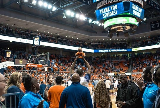 Auburn's Anfernee McLemore holds son Maverick over his head as he walks onto the floor during senior night against Texas A&M on March 4, 2020.