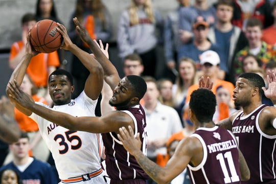 Auburn guard Devan Cambridge (35) passes the ball around Texas A&M forward Jonathan Aku (15) during the first half of an NCAA college basketball game Wednesday, March 4, 2020, in Auburn, Ala. (AP Photo/Julie Bennett)
