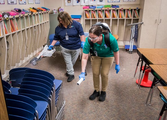 Custodian Amanda Rogers  and custodial manager Jennifer Locke disinfect North View Elementary School with a fogging gun after school Wednesday.