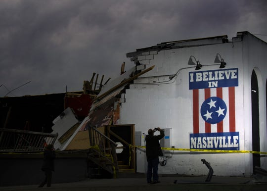 "Marc Kuhns takes a picture of the ""I Believe in Nashville"" mural at The Basement East on Wednesday, March 4, 2020, a day after a tornado ripped through the city."