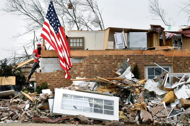 Greg Owen places a flag that was found in the rubble of a home on Barrett Drive after a tornado hit Mt. Juliet, Tenn.