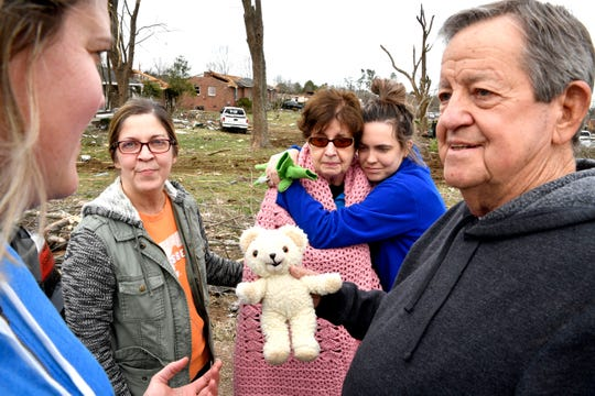 """Bill Wallace holds a """"baby bear"""" that was found in the rubble of his home as his granddaughter Samantha Leonard hugs his wife Shirley while daughter Sonya Leonard looks on. The couple returned to the house where they were trapped when it fell on them during the tornado in Mt. Juliet, Tenn. Wednesday, March 4, 2020."""