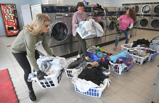 Amy Thompson, left, and other volunteers help wash tornado victims' clothing for free at A-1 Coin Laundry in Cookeville, Tenn., on Thursday, March 5, 2020.