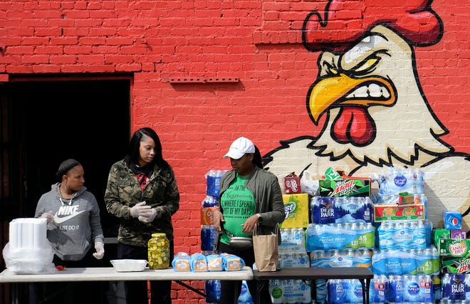 Chantee Whitworth, left, Kyoko Wade, and Kendra Campbell of Rocky Wing Shack prepare food for people helping clean up tornado debris on Thursday, March 5, 2020, in North Nashville, Tenn.