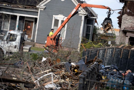 A Public Works worker clean debris on South 11th Street on Thursday, March 5, 2020, in East Nashville, Tenn.