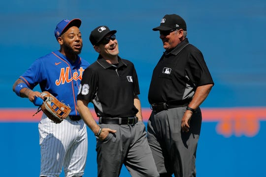 Third base umpire David Rackley, center, and second base umpire Hunter Wendelstedt, right, react as New York Mets Dominic Smith makes a comment at the end of the first inning of a spring training baseball game against the St. Louis Cardinals, Wednesday, March 4, 2020, in Port St. Lucie, Fla.