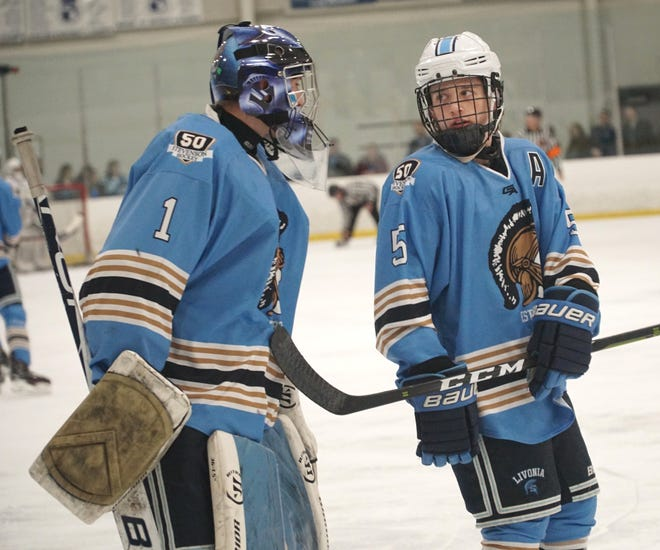 Spartan forward Brenden Heard, right, confers with his goalie Brenden Stroble during Stevenson's March 4, 2020 playoff game against Novi High.