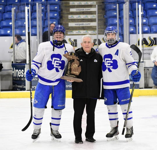 CC Captain Dylan Dooley pose with Father Dennis Kauffman along with Enzo Tarducci with the regional Trophy.