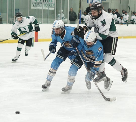 Novi Wildcat Isaac Gibbs rides up the back of a Spartan as he tries to get to the puck during the teams' March 4, 2020 playoff game.