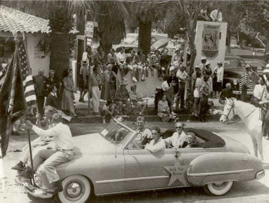 Large crowds watch as Safrona Gill, mother of Marine Pfc. Richard Gill, who was killed in combat in Guadalcanal on Nov. 10, 1942, is honored as a Gold Star Mother in a Desert Circus parade in downtown Palm Springs. Safrona Gill is sitting in the backseat, on the driver's side.